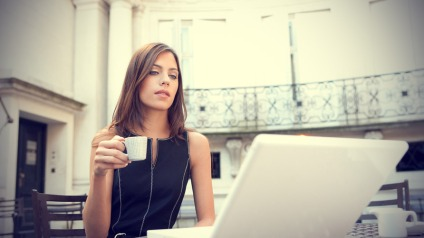 Young-attractive-businesswoman-sitting-in-a-luxurious-coffee-shop-terrace-with-her-laptop